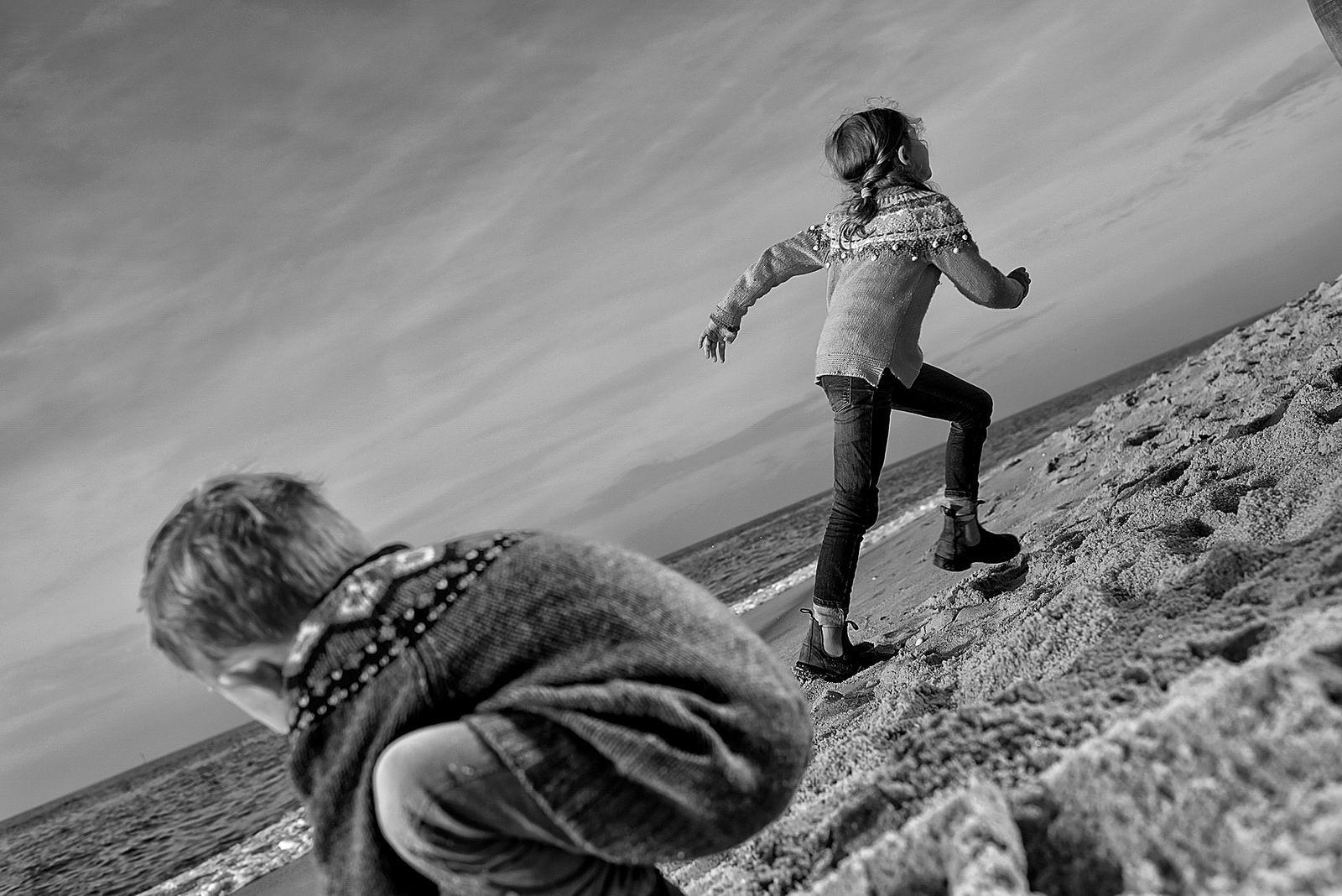 Zwei Kinder spielen am Strand auf Westerland auf der Insel Sylt. Ein kleiner Junge baggert in den sand und seine ältere Schwester rennt gerade weg