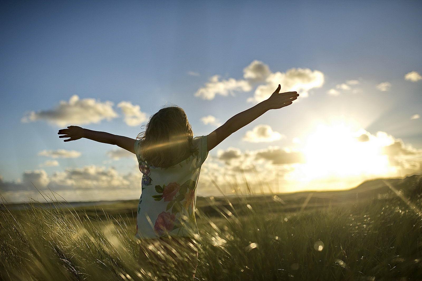 Ein Kind in Dünen am Ellenbogen auf Sylt spritzt die Ärme und schaut gegen den Sonnenuntergang