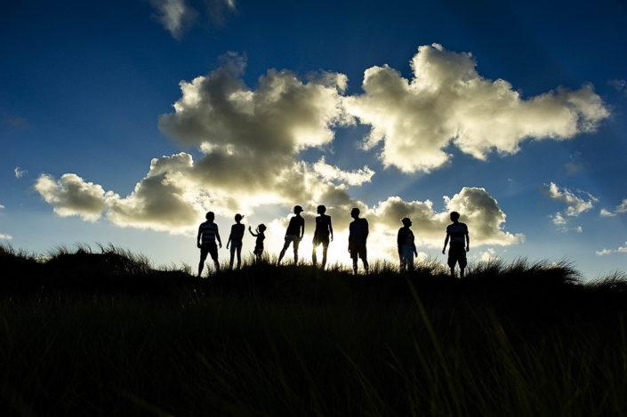 Achtköpfige Familie steht oben auf der Düne, man sieht nur die Silhouetten, in Hintergrund ist eine Wolkenlandschaft und dahinter untergehende Sonne.