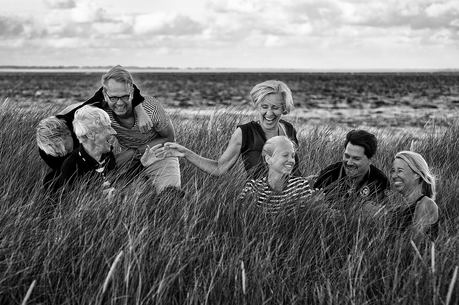 Eine Familie hockt in den Dünen in List. die kitzeln sich gegenseitig und lächeln dabei herzlich