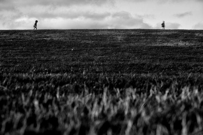 In sylter Heidelandschaft stehen 2 Kinder oben auf dem Wall und schauen sich an