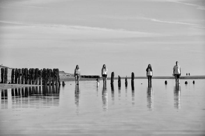 Eine vierköpfige Familie steht starr und gerade im flachen Wasser der Sandbank auf der Westküste von Sylt, ihres Spiegelbild sieht man in der Meeroberfläche. Die Buhnen kompletieren das Bild