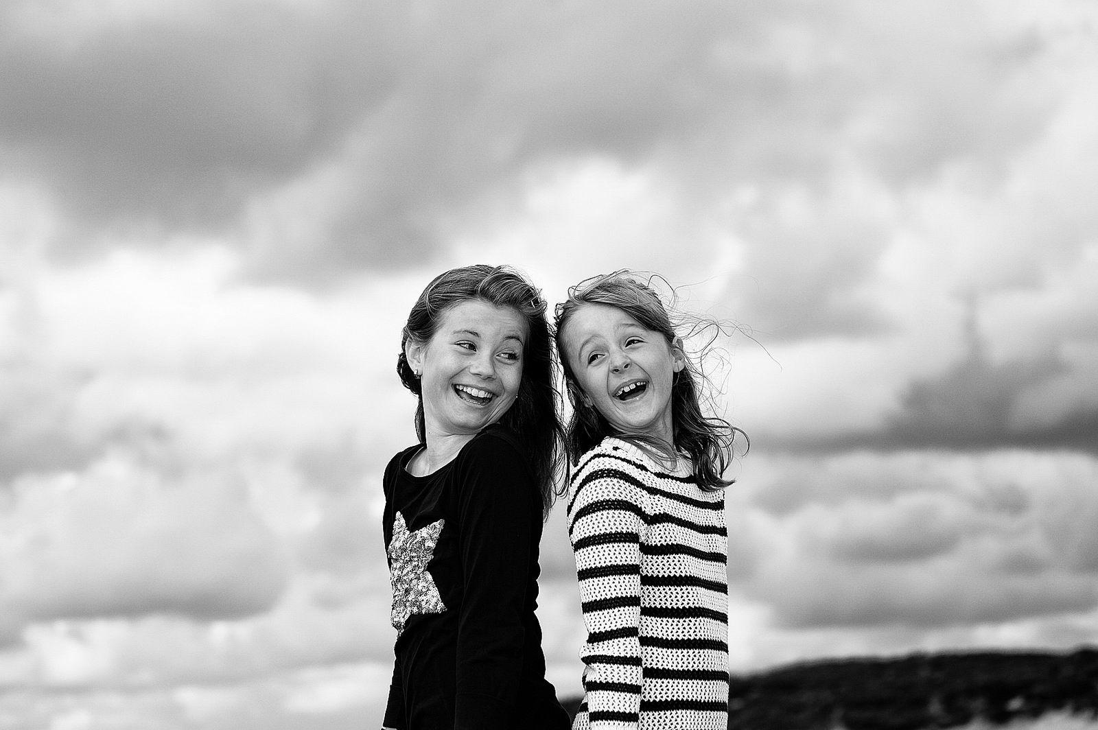 Zwei Mädchen posieren für den Fotografen vor der morsumer Wattlandschaft auf der Insel Sylt. Sie stehen Rücken am Rücken und lächeln herzlich