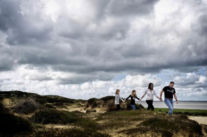 Eine vierköpfige Familie wandert Hand in Hand in der wunderschöner morsumer Landschaft. Im Hintergrund sieht man das Wattenmeer.